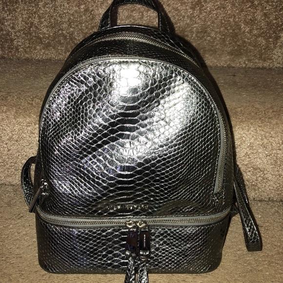 60d0e0fe8ea0 Michael kors rhea metallic silver backpack. M_5b46122c2e14785a8b655347
